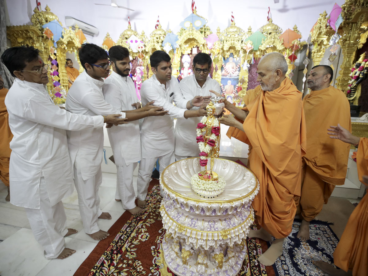 Swamishri and youths  perform abhishek of Shri Nilkanth Varni