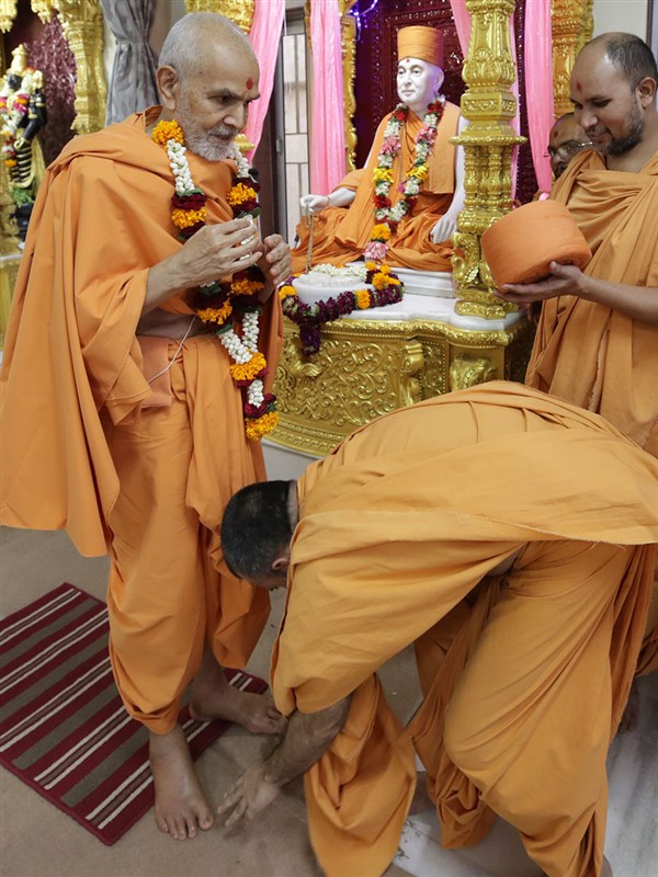 Anandsagar Swami honors Swamishri with a garland