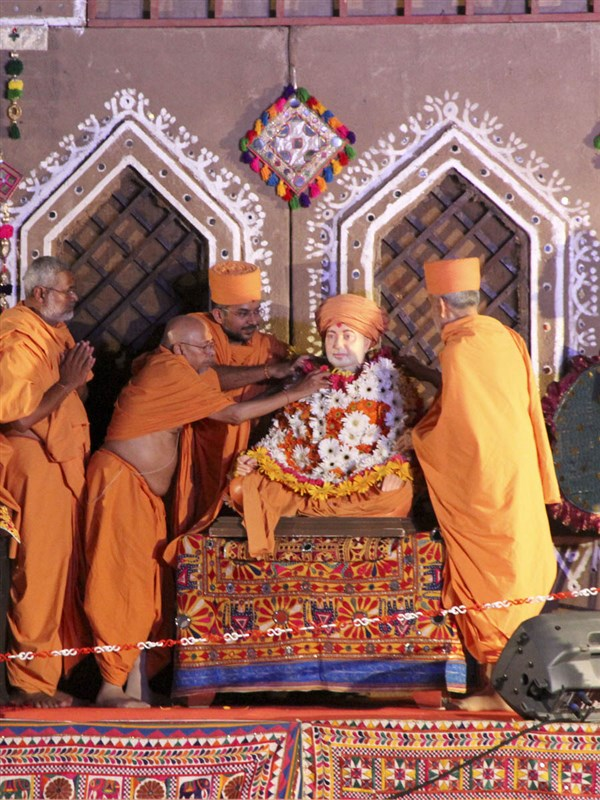 Swamishri and Pujya Tyagvallabh Swami honor Brahmaswarup Pramukh Swami Maharaj with a shawl