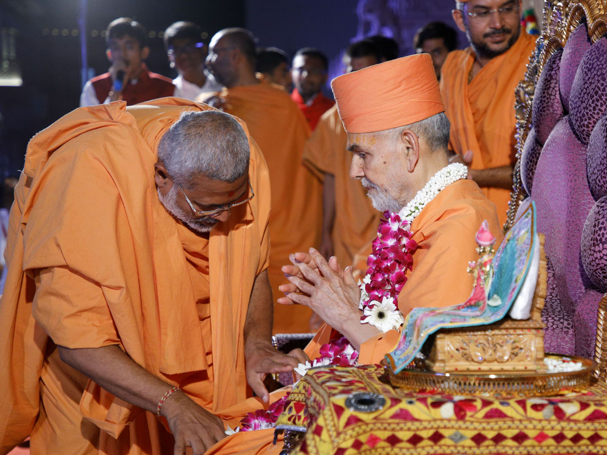 Brahmatirth Swami welcomes Swamishri with a garland