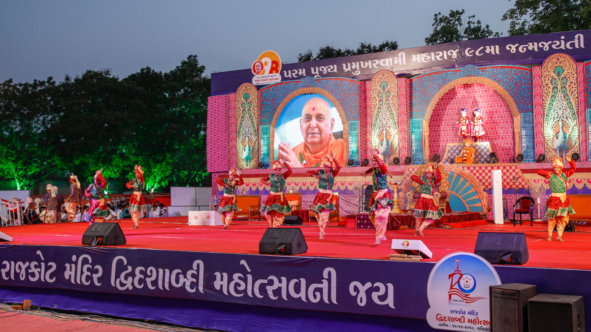 Youths perform a traditional dance in the evening satsang assembly to mark the beginning of Pramukh Swami Maharaj's 98th Birthday Celebrations and Rajkot Mandir Dwi-Dashabdi Mahotsav