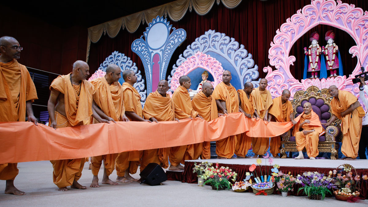 Sadhus honor Swamishri with a vastra seva