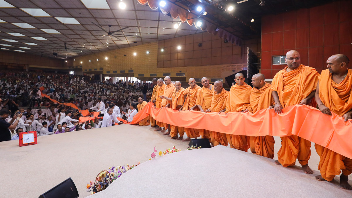 Sadhus and devotees honor Swamishri with a vastra seva
