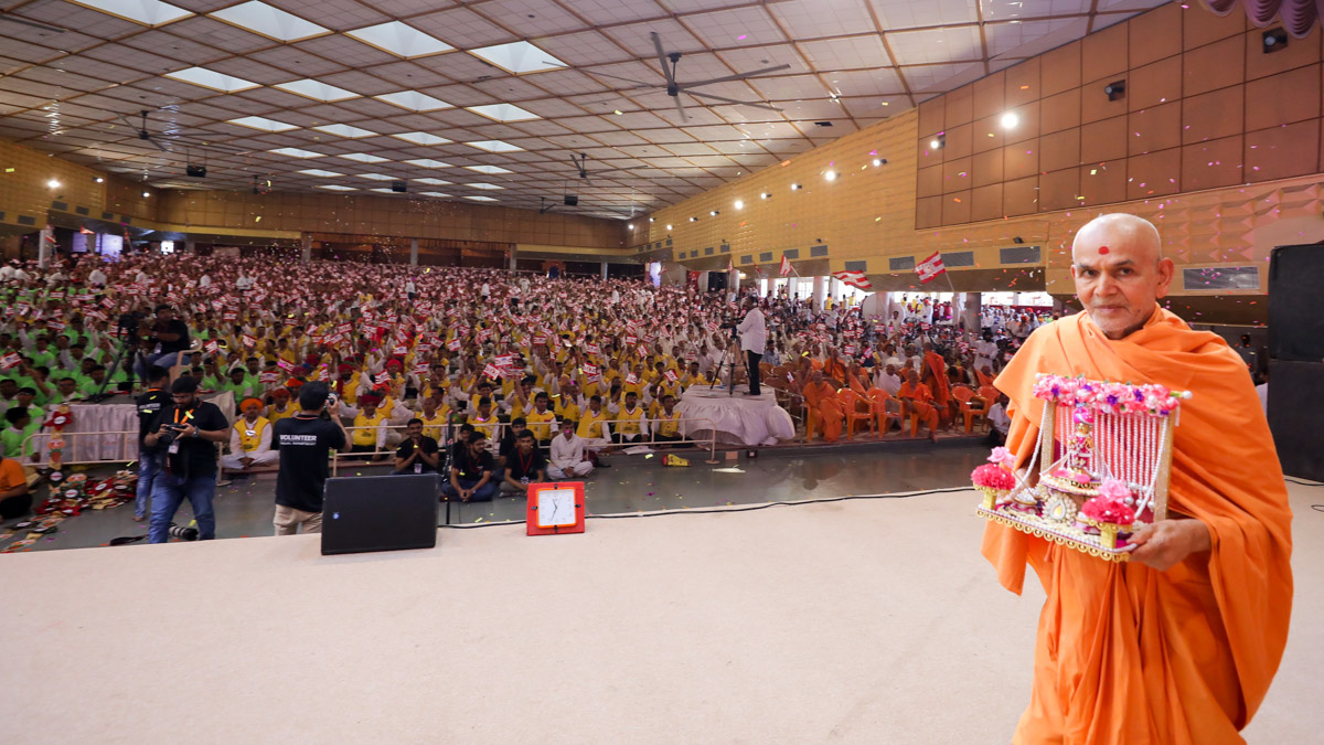 Swamishri  arrives in the morning volunteers' assembly with Shri Harikrishna Maharaj