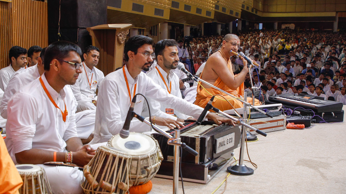 Youths sing kirtans in Swamishri's puja