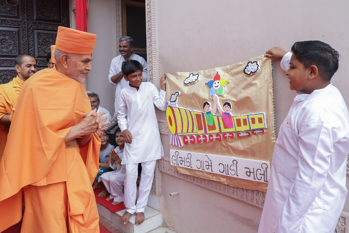 Children display a banner before Swamishri