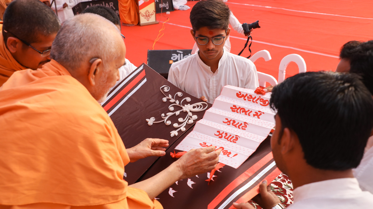 Swamishri sanctifies an invitation card for evening Yuva Din assembly