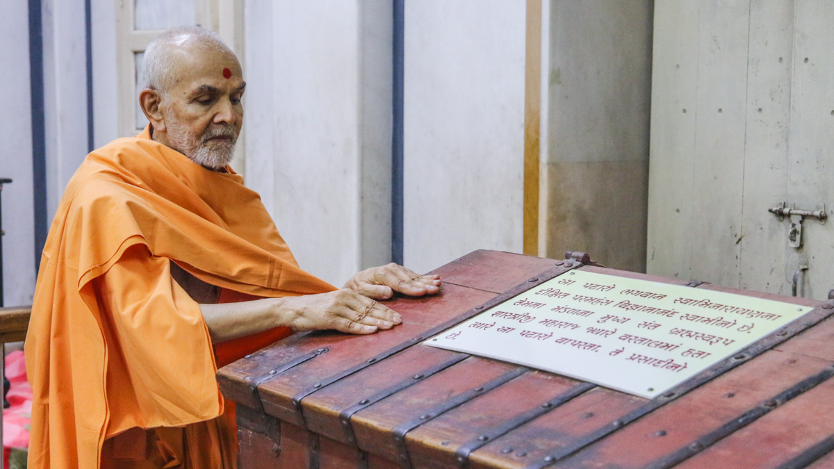 Swamishri reverentially touches sacred 'pataro' in the Rang Mandap