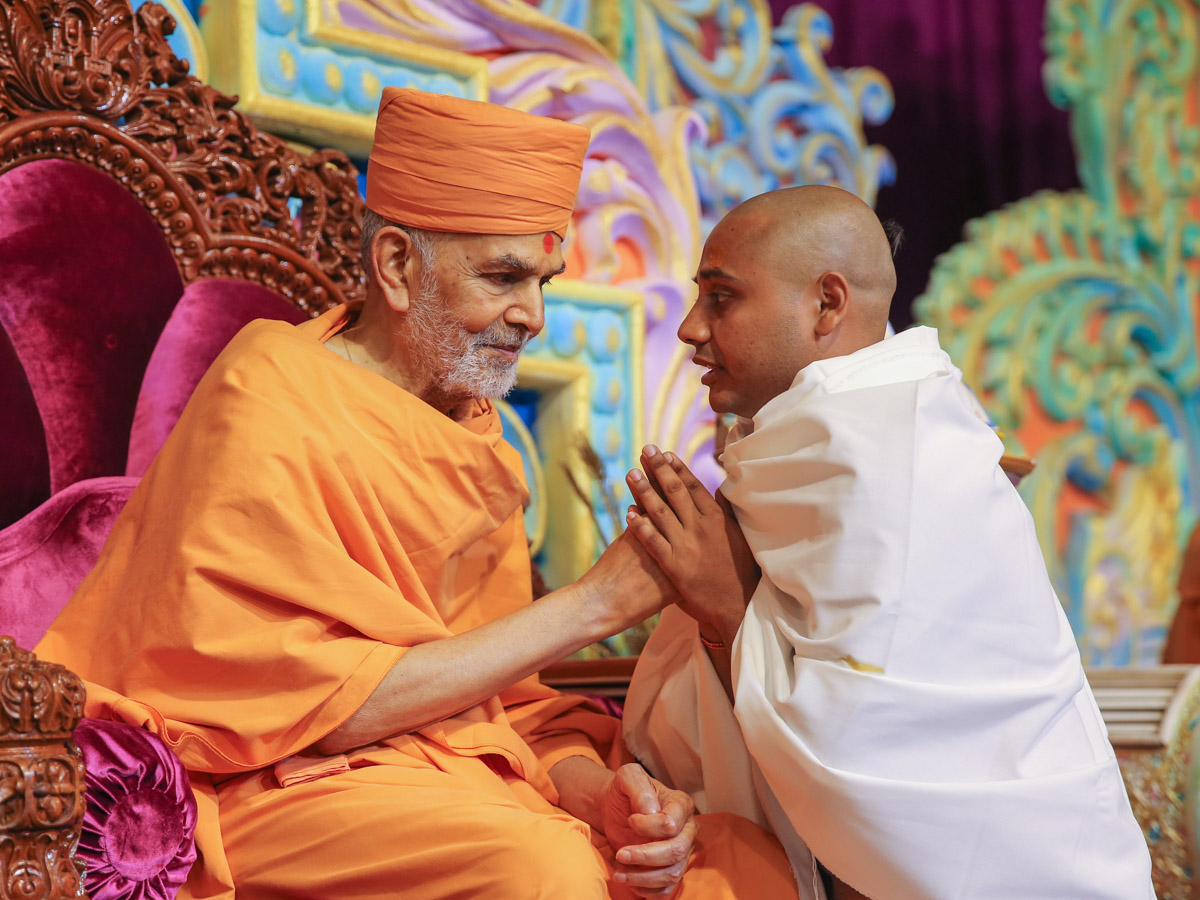 Swamishri gives diksha mantra to newly initiated parshad