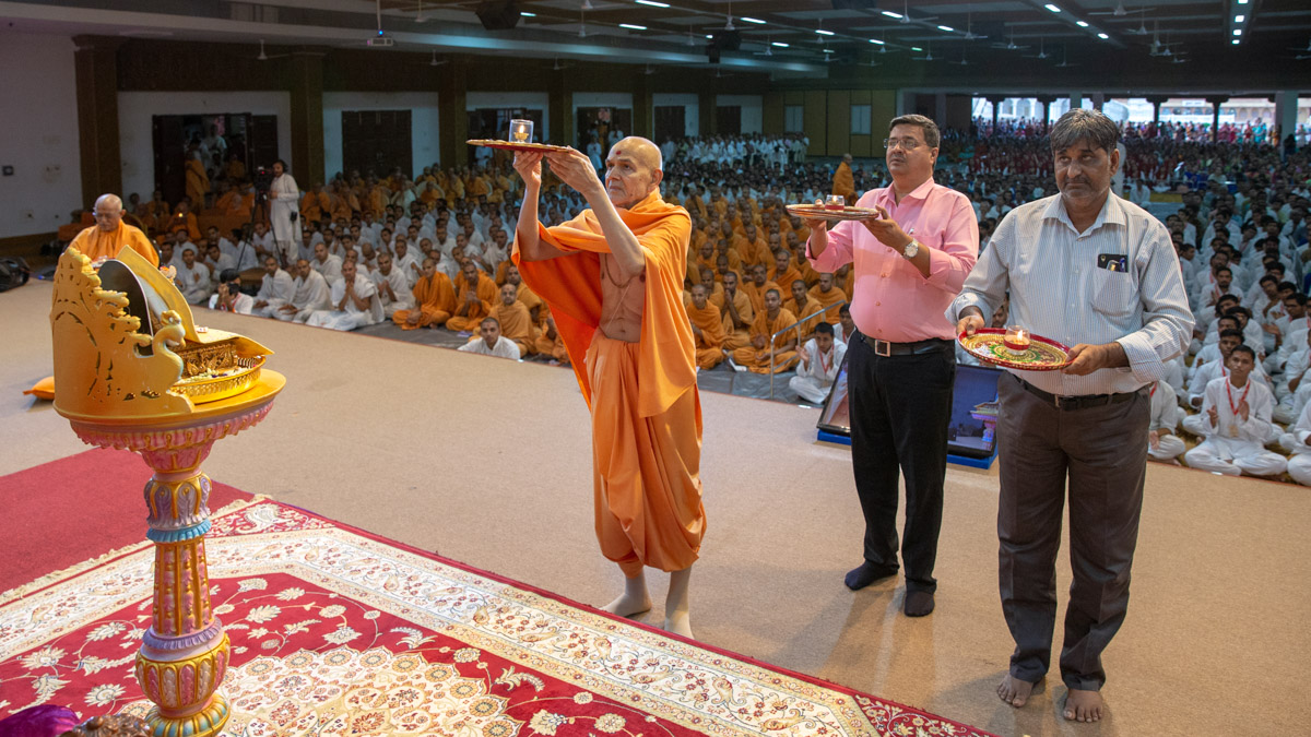 Swamishri and invited guests perform the evening arti