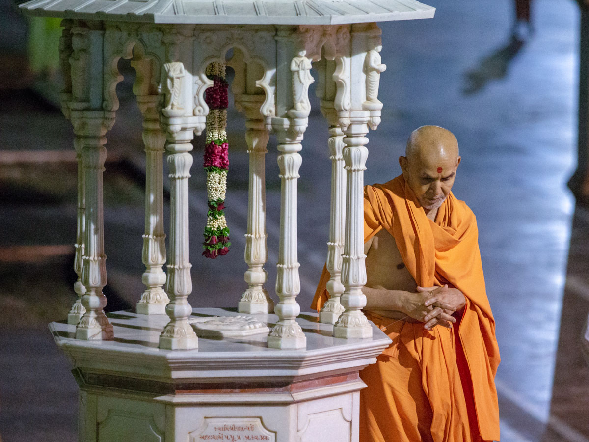 Swamishri performs pradakshina of the holy charanarvind of Bhagwan Swaminarayan in the evening