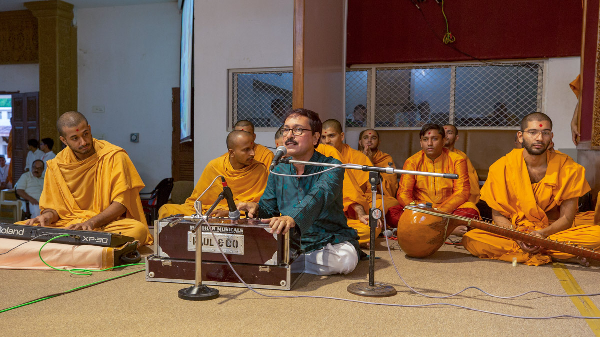 A youth sings kirtans in Swamishri's morning puja
