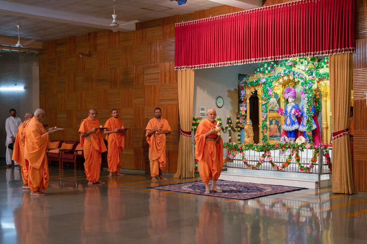 Swamishri performs arti in the Vidyamandir assembly hall