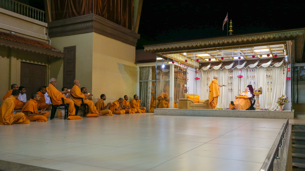 Swamishri and senior sadhus perform the evening arti in the Pramukh Mandiram