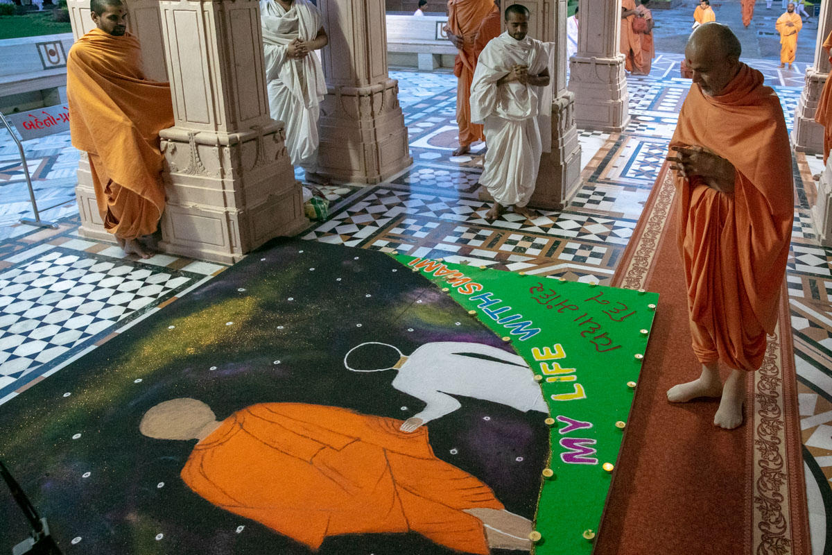 Swamishri observes a rangoli at the Smruti Mandir
