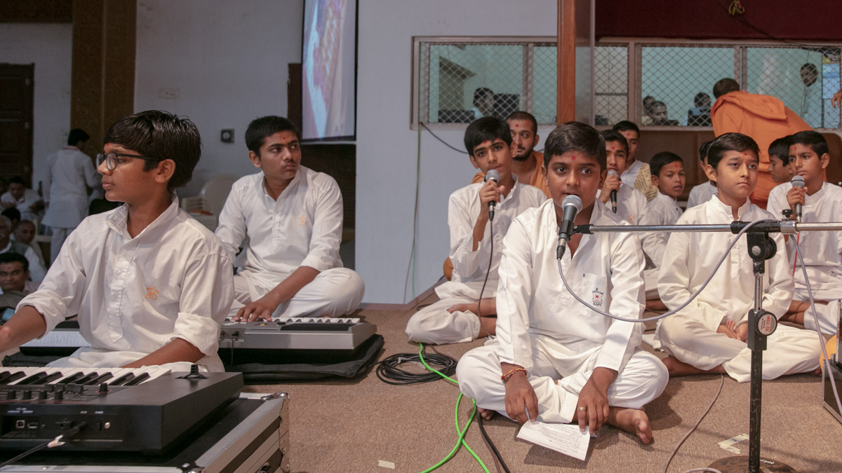 Students sing kirtans in Swamishri's puja