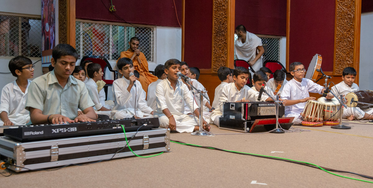 Students sing kirtans in the evening assembly