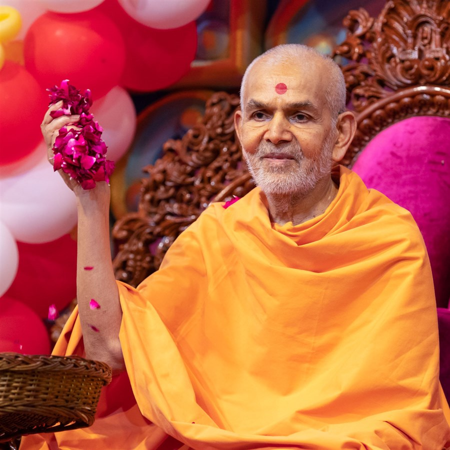 Swamishri showers flower petals on students