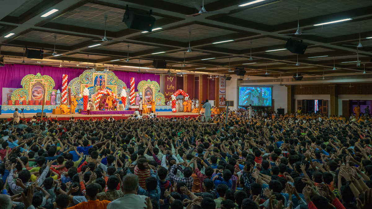 Students gesture to embrace Swamishri