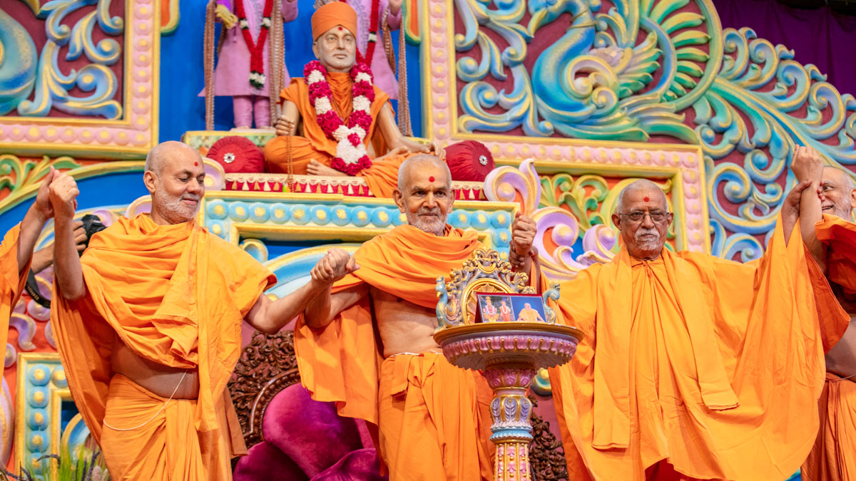 Swamishri and senior sadhus join hands in a gesture of unity
