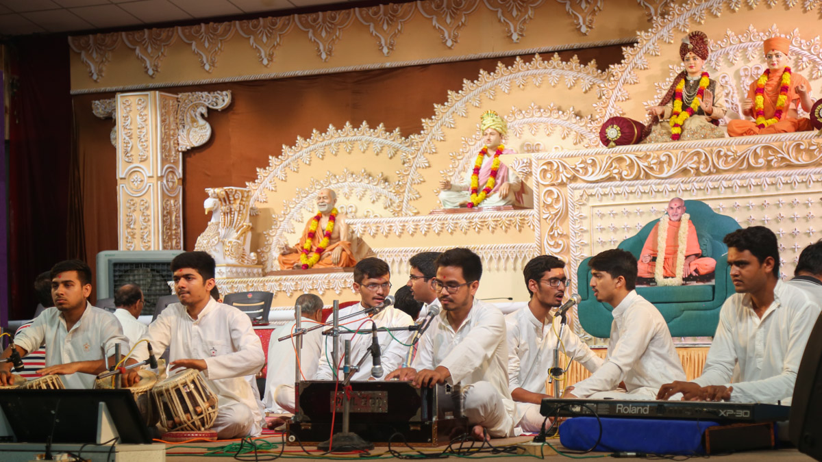 Youths sing kirtans in the evening welcome assembly
