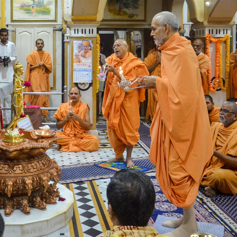 Swamishri and Pujya Tyagvallabh Swami perform the morning arti of Shri Nilkanth Varni in the Rang Mandap