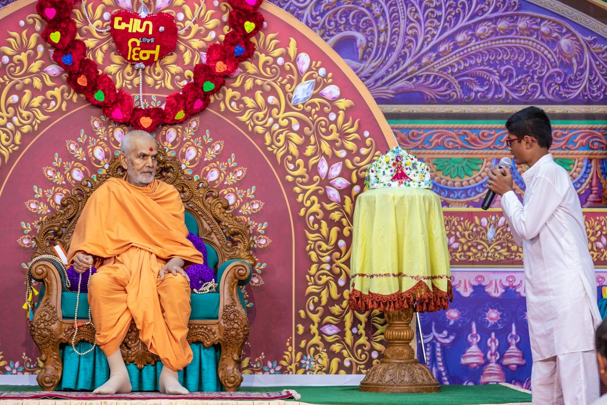 A child presents before Swamishri during the evening Bal Din assembly