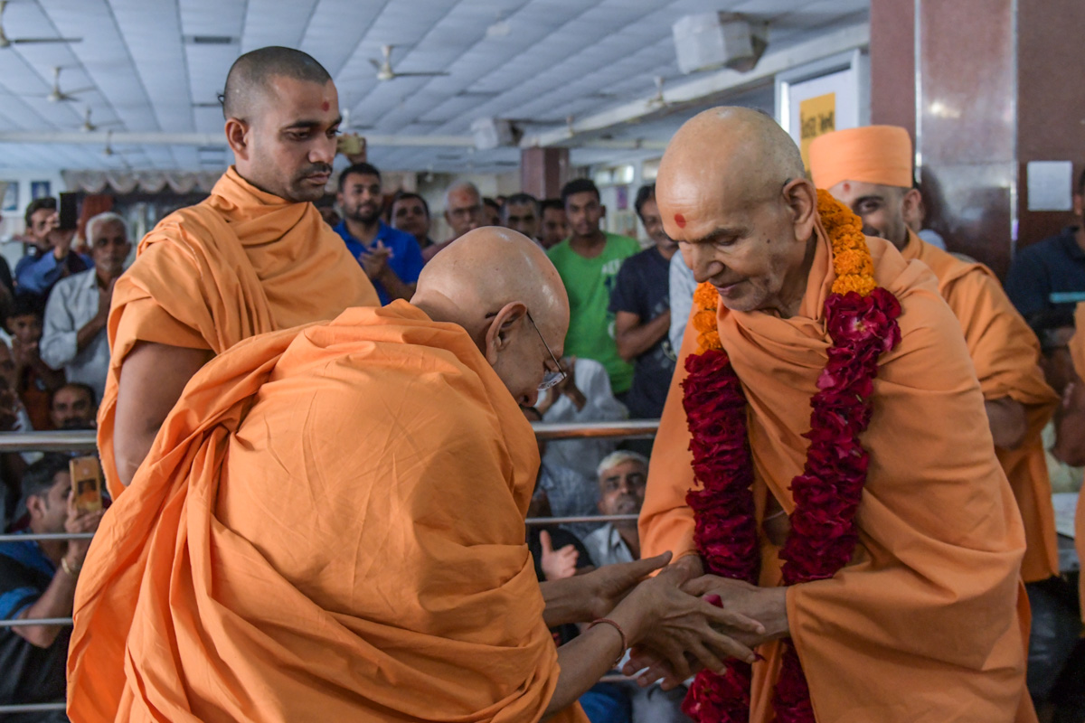 Pujya Tyagvallabh Swami honors Swamishri with a garland as he departs from Bochasan in the afternoon