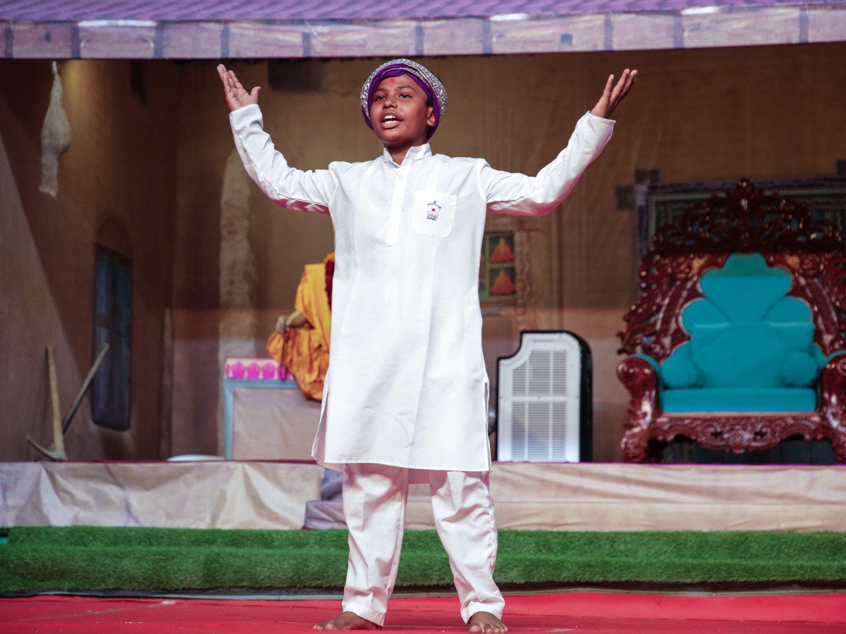 A tribal child presents in the evening Vanvasi Din satsang assembly