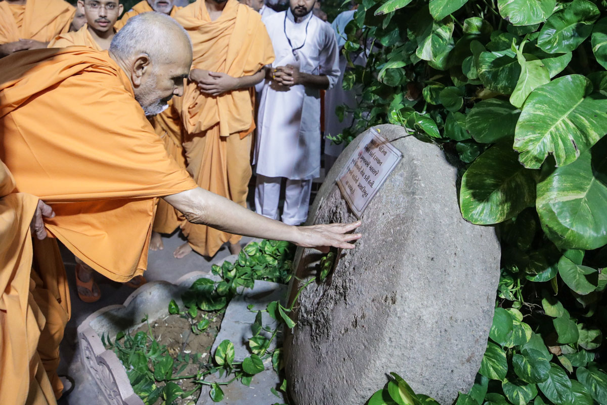 Swamishri reverentially touches a sacred stone used by Pramukh Swami Maharaj to prepare lime for the construction of Atladra Mandir over 70 years ago