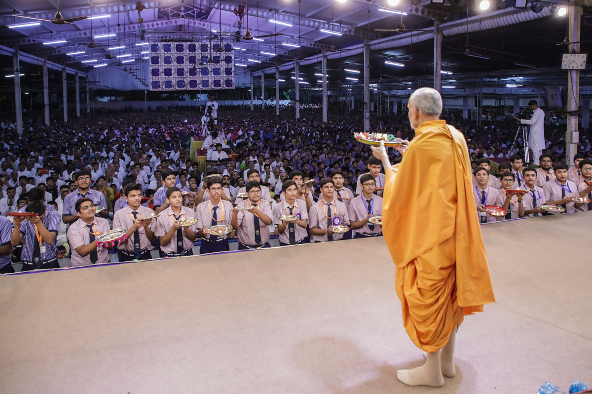 Swamishri and students perform the evening arti
