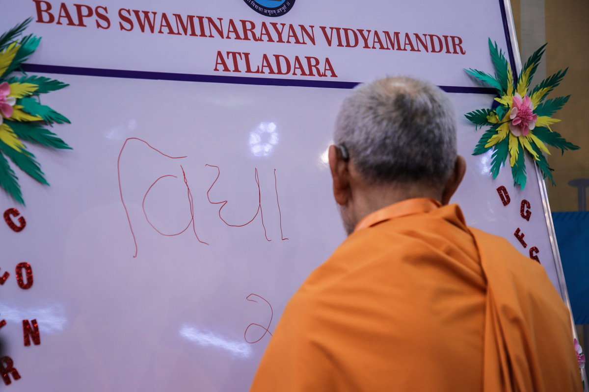 Swamishri writes blessings on a board