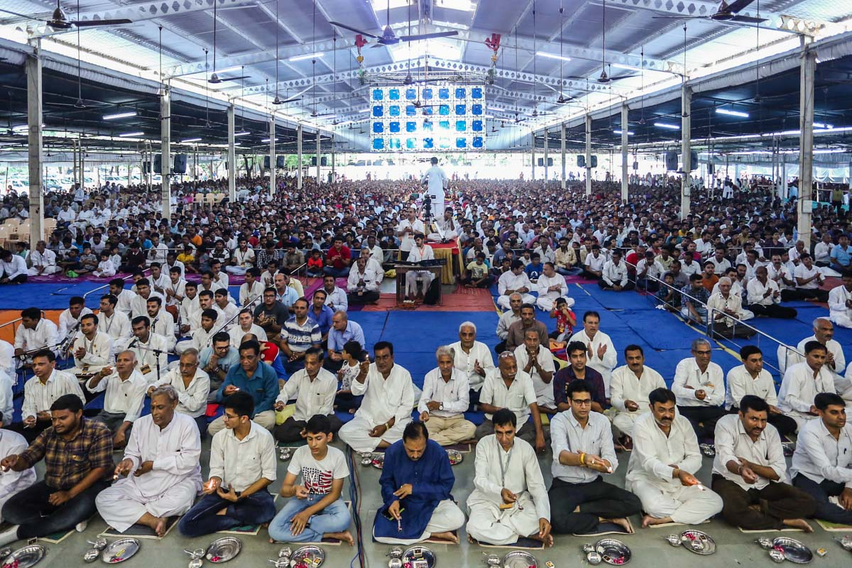 Devotees participate in the parayan pujan in the evening assembly