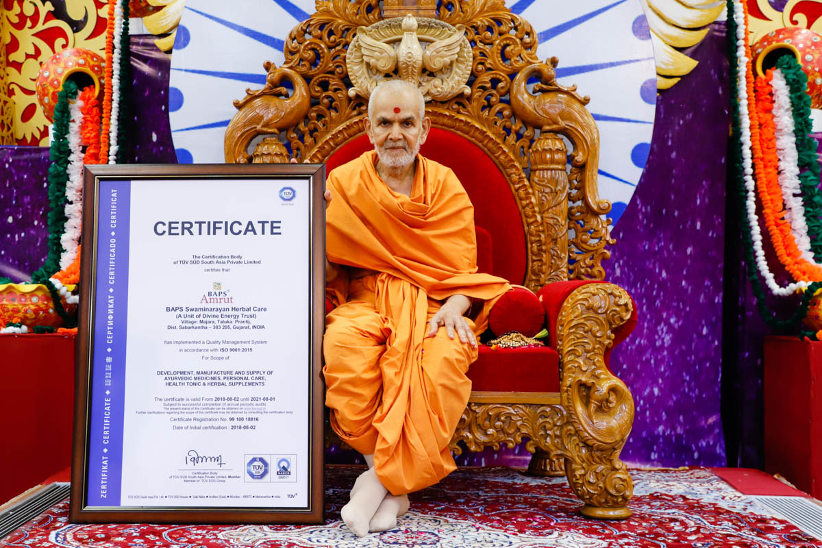 Swamishri sanctifies an ISO 9001:2015 certificate awarded to BAPS Swaminarayan Herbal Care
