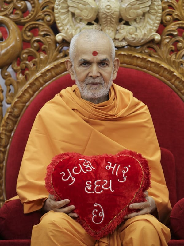 Swamishri sanctifies a heart-shaped cushion