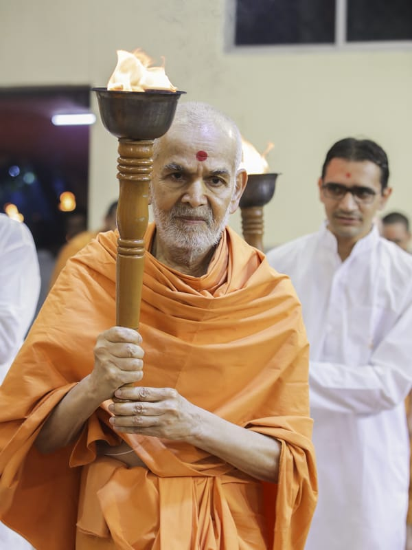 Swamishri leads youths with a torch