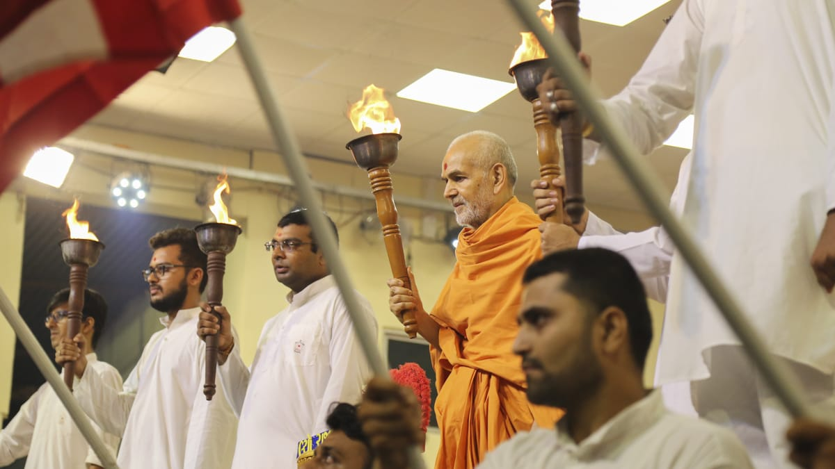 Swamishri and youths with mashals (torches)