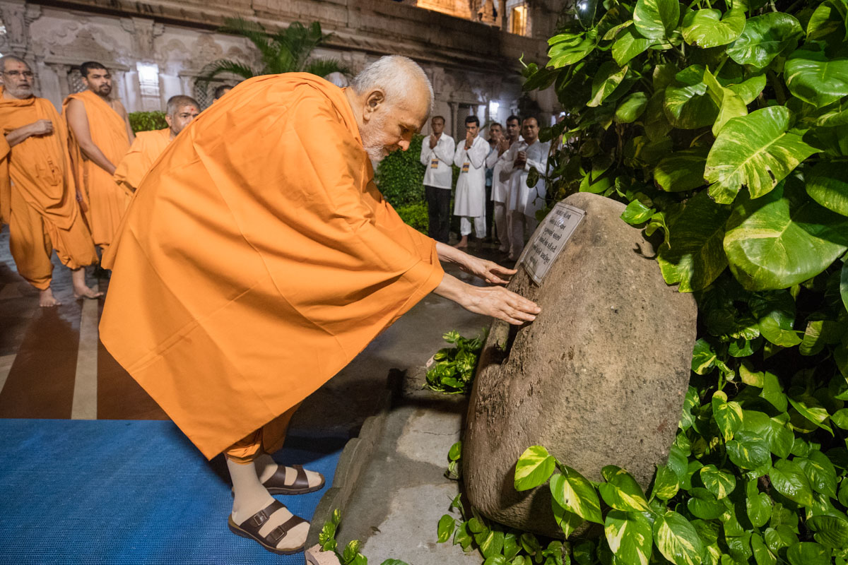 Param Pujya Mahant Swami Maharaj reverentially touches a sacred stone once used to make mortar in the time of Shastriji Maharaj