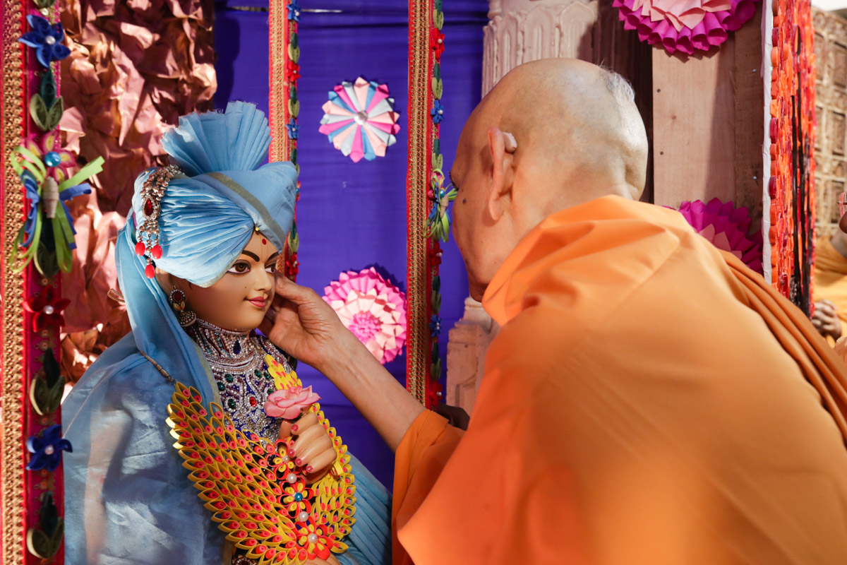Swamishri decorates the murti of Bhagwan Swaminarayan installed in the hindolo