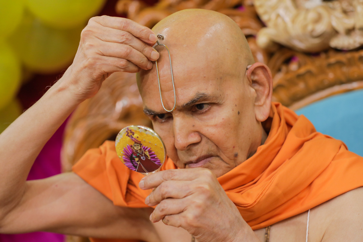 Swamishri applies tilak in his morning puja