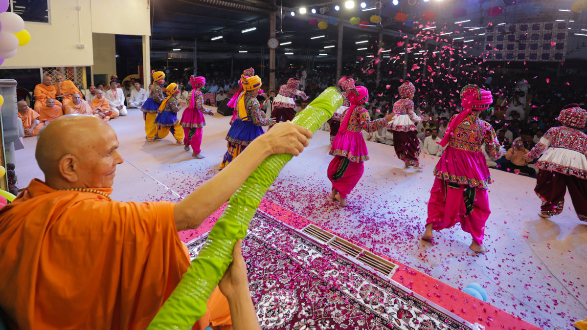 Swamishri showers flower petals on children