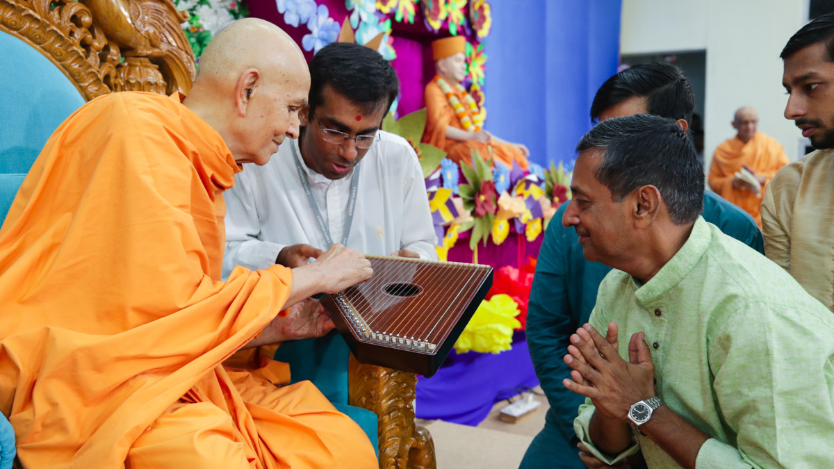 Swamishri sanctifies a swarmandal (an Indian harp)