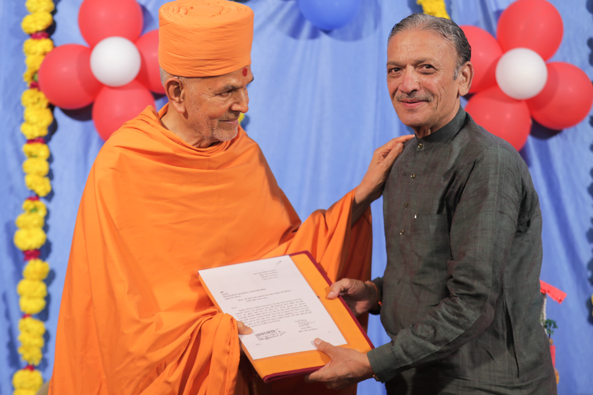 Shri Narhari Amin presents letter to Param Pujya Mahant Swami Maharaj confirming government approval of Chansad village development project