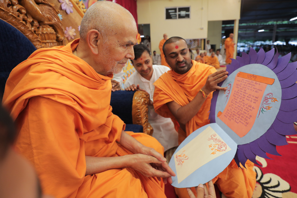 Swamishri sanctifies a prayer card prepared by youths