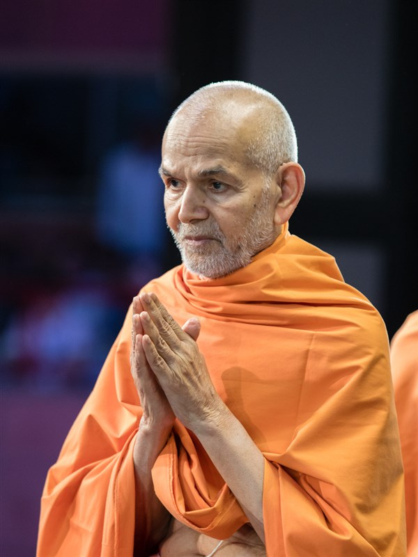 Swamishri greets devotees with 'Jai Swaminarayan' in the assembly hall