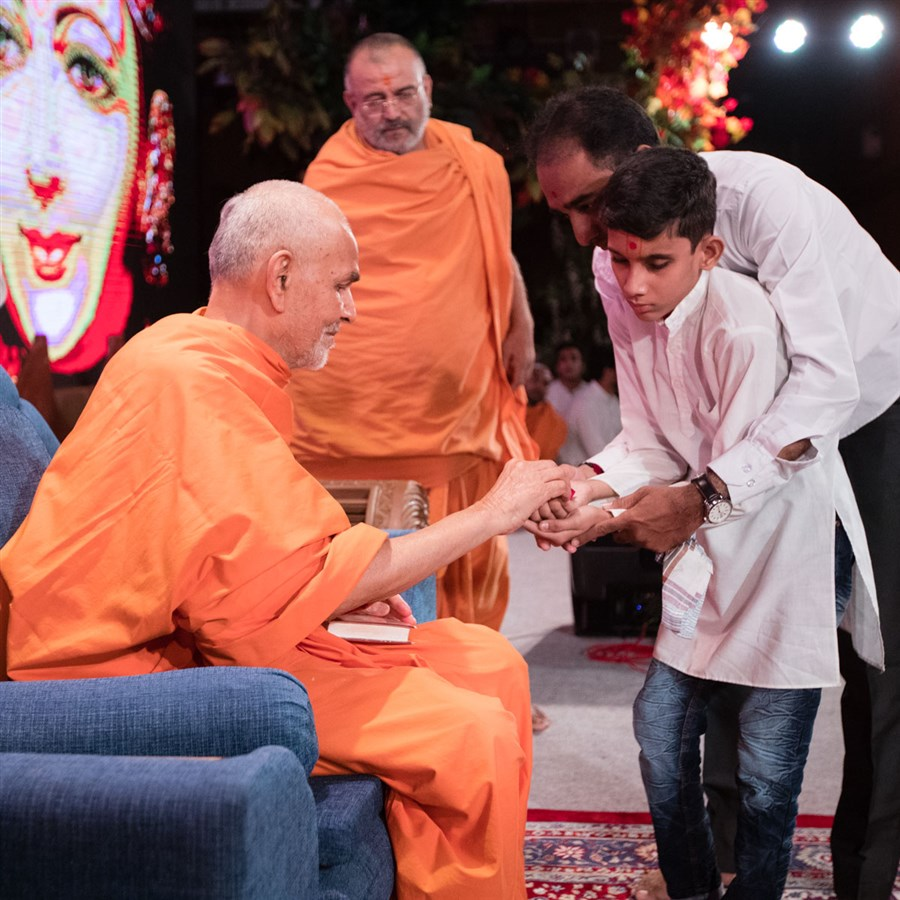 Swamishri blesses a blind child who sang kirtans in his morning puja