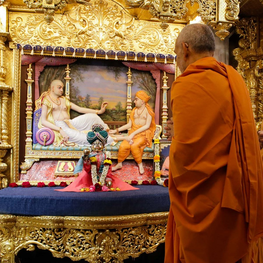 Swamishri engrossed in darshan of Shri Lalji Maharaj in the Sukhshaiya