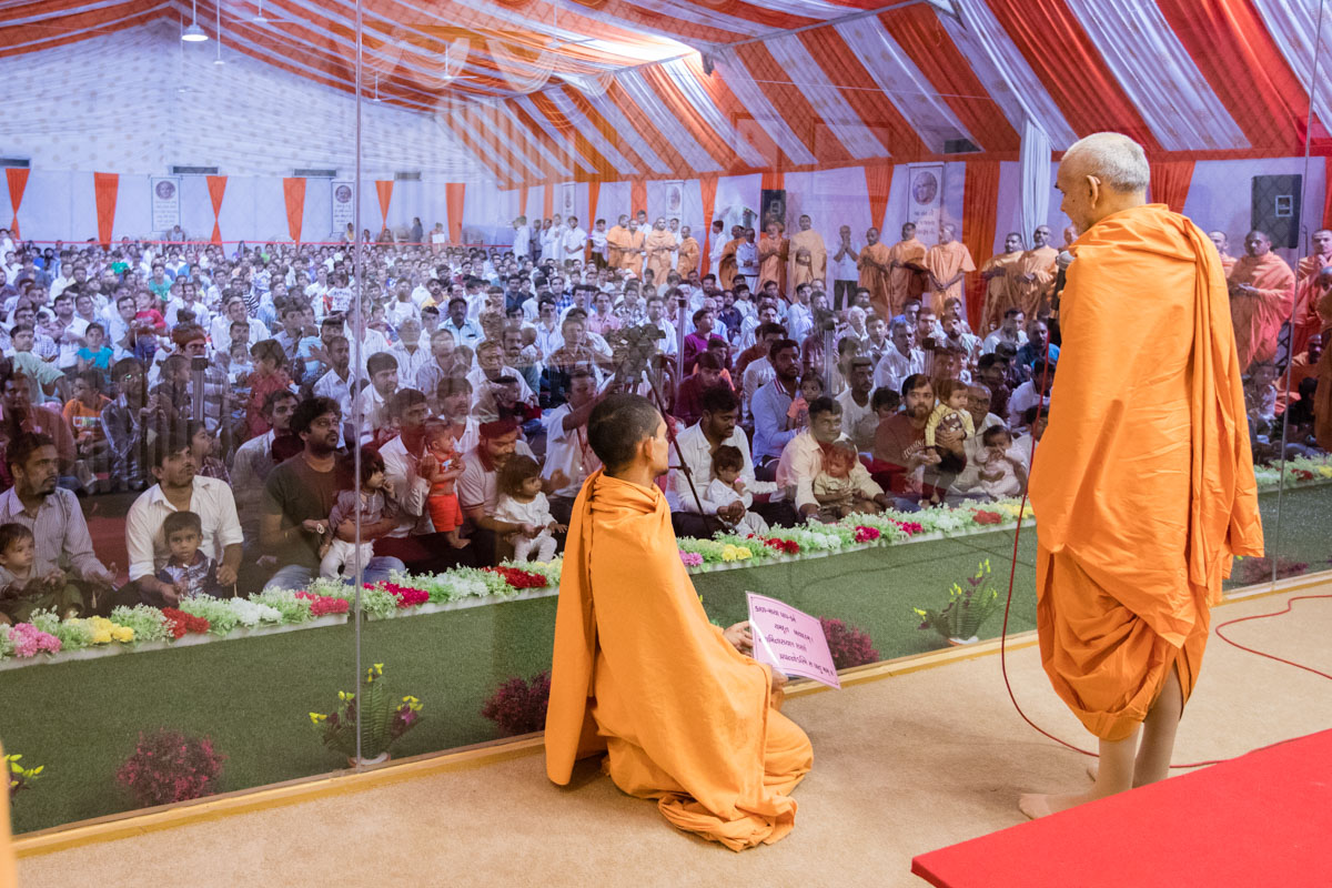 Swamishri gives vartaman to children and devotees