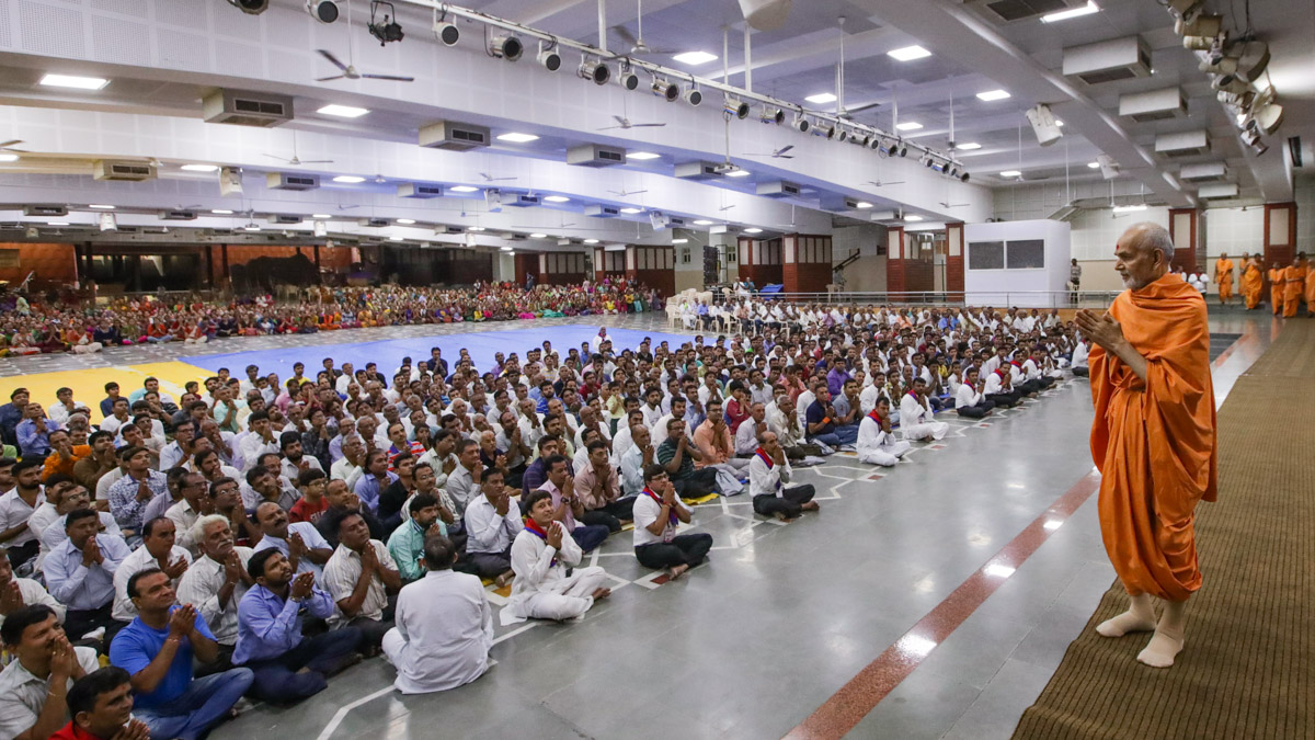Swamishri greets devotees with 'Jai Swaminarayan' in the Pramukh Swami Auditorium