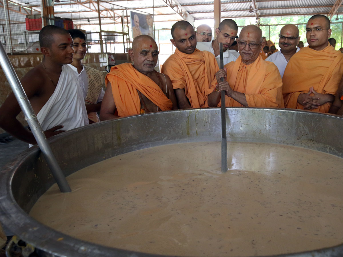 In the afternoon, Pujya Doctor Swami helps in the preparation of dudhpak for Shastriji Maharaj's Smruti Parva